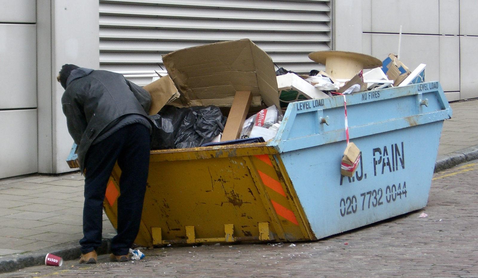 Immagine di un barbone che fruga nel'immondizia: Tecnica Dumpster Diving